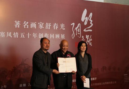 中华世纪坛艺术基金会的周围女士和赵长岭先生向舒春光先生颁发作品捐赠收藏证书