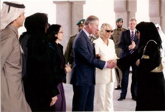 """2016年,英国王储查尔斯王子(HRH Prince Charles)亲自出席娜迪雅公主的""""英国油画艺术展"""",双方亲切握手表达友好情谊,对娜迪雅公主在艺术上的成就表示了赞赏。卡塔尔前国王哈马德陛下(图左二)领衔为娜迪雅公主在英国皇宫举办油画艺术大展,推广卡塔尔的艺术与文化。"""