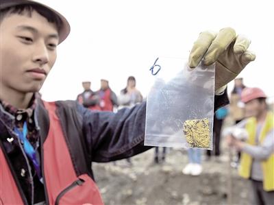 考古人员在发掘现场展示出水文物。新华社发
