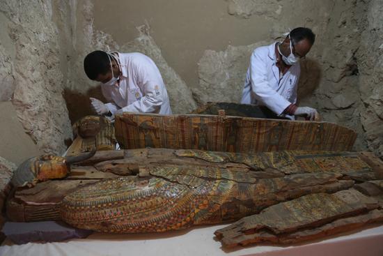 埃及古城卢克索,考古人员清理乌塞尔哈特墓出土的文物。新华社发(艾哈迈德・戈马摄)