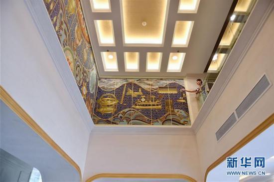 """5月11日,在故宫鼓浪屿外国文物馆,解说员冯晓如在馆内描绘着""""海丝""""和西洋文物的巨幅掐丝珐琅画前练习解说。"""