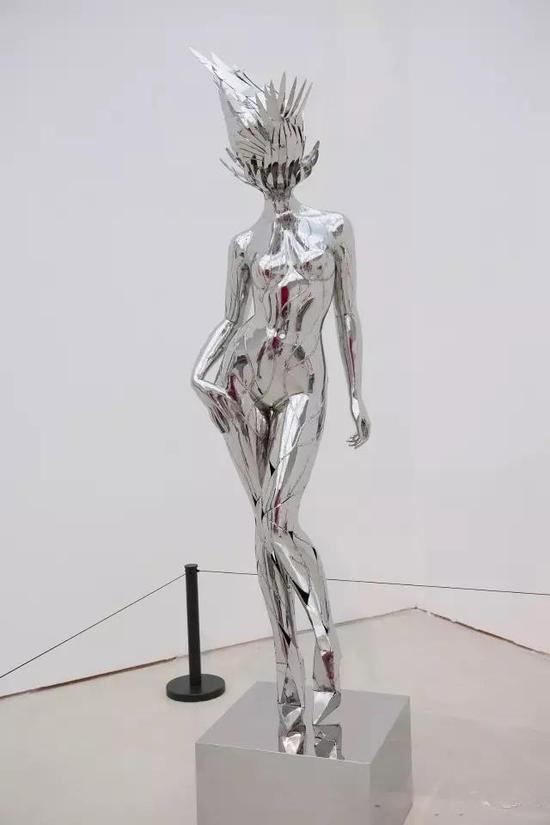 """侯雯 《MUSE》 不锈钢 造型学院雕塑系,指导教师:隋建国、吕品昌、张伟、于凡、展望、王少军 """"底部无序的不锈钢碎片拼接在一起逐步往上焊接,形成具体的女人体。到头部则是逐渐变为有序的不锈钢羽毛片组成的抽象形态。女人体的姿态稍微仰头,头部有一种原始头饰般夸张神圣的意味,正如同神话中缪斯用塞壬女妖们的翅膀编织成了象征她们胜利的王冠。"""""""
