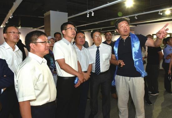 中国美术家协会油画艺术委员会秘书长、中国艺术研究院中国油画院副院长徐青峰(右一)为嘉宾介绍展览作品