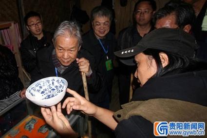 贵州省考古所副所长李飞正向北京大学教授李伯谦等人介绍一件出土瓷器