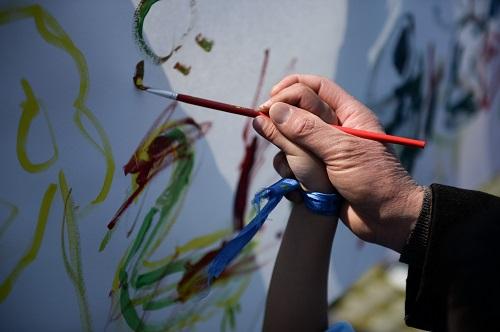 """资料图片:4月2日,合肥市孤独症康复协会等机构组织的""""照亮来自星星的孩子""""世界自闭症日公益宣传活动在合肥市杏花公园举行,这是一名自闭症儿童和家长在活动现场绘画。新华社记者 张端 摄"""