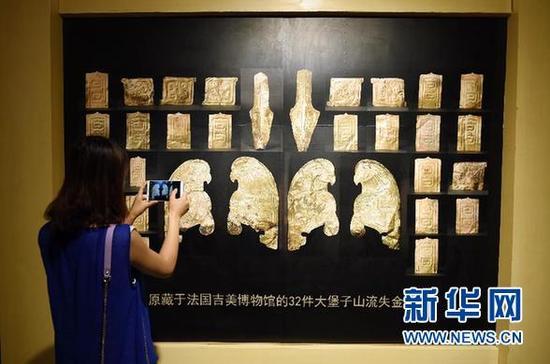 7月20日,在甘肃省博物馆,一位观众拍摄法国无偿归还我国的32件流失文物的展览图。新华社记者 范培珅 摄