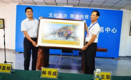 刘勇董事长代表筹备单位和中广双向凉山州委赠送曹勇油画《重返梁家河》的限量复制品