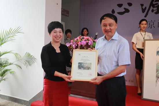 桂林市花桥美术馆馆长邱丽萍向北京画院院长王明明颁发收藏证书。