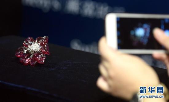9月12日,参观者拍摄红色碧玺配钻石别针。当日,香港苏富比珠宝首饰秋拍举行传媒预展。本季拍卖共计推出超过250件拍品,总估值约合5.4亿人民币。 新华社记者 秦晴