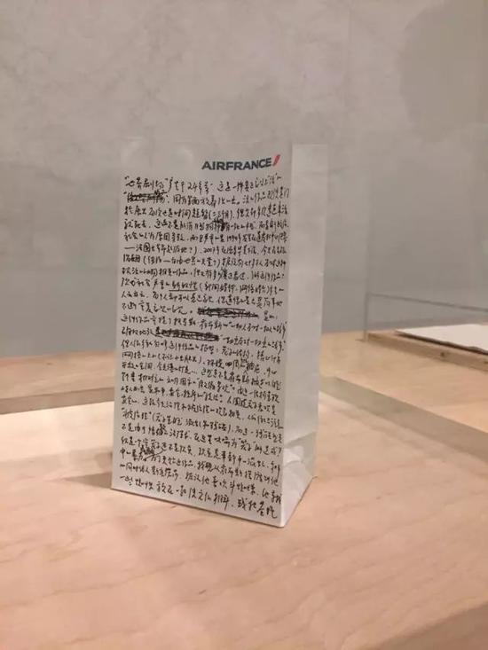 黄永砅被撤下的作品旁,艺术家亲手在航班呕吐袋上写的《艺术家声明》。图片:Cathy Fan