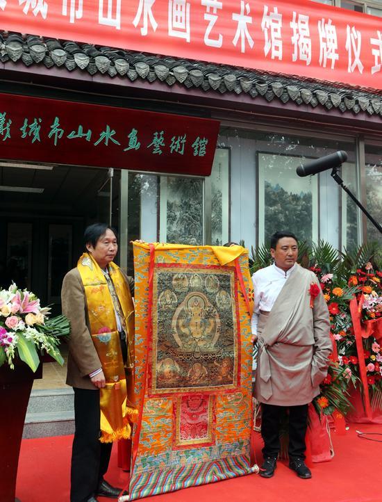 来自青海热贡的藏族唐卡绘画大师吉合它加为祝贺杨留义城市山水画艺术馆揭牌,特地献上哈达和吉祥如意唐卡