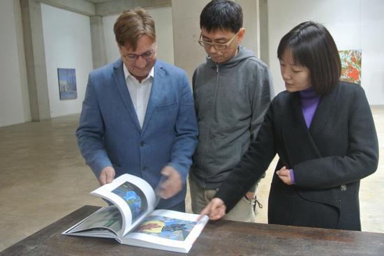 参展艺术家安东尼(左一)和现场嘉宾观看画册