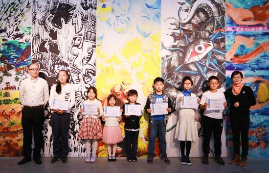 新美杯大赛评审组委会委员、中国美院设计学院讲师罗凌霞老师;上海市世界外国语中学艺术学科组长沈岭老师为三等奖获得者颁发获奖证书