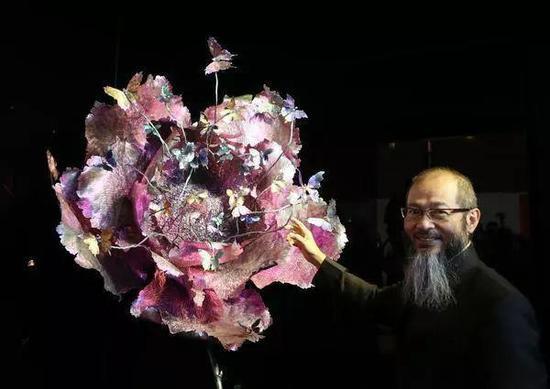 2015年11月28日陈世英在香港会展中心举行的其个人作品《梦光水》展览上,向嘉宾介绍他最新创作的大型珠宝艺术作品《心花振翅》