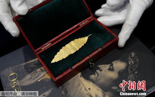 拍卖师展示一片黄金月桂叶,这片金叶子曾是拿破仑加冕礼皇冠上的几十片金叶子之一。