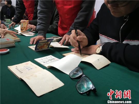 图为连环画大师为书迷签名 李佳赟 摄