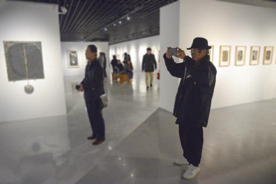 """""""八三年阶段绘画实验展览""""参展艺术家方昉在展厅观画并拍摄做留念"""