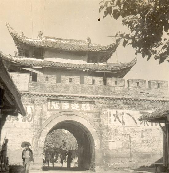 """广汉西城门,重檐歇山顶的门楼,劵拱上写着""""驱除倭寇""""四个大字,城墙上""""万众一心""""美术字也清晰可见"""