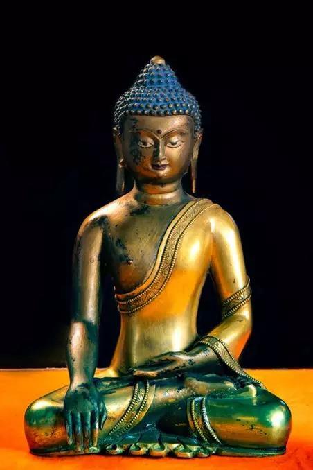 (宗教文化艺术展品赏析/铜鎏金释迦牟尼佛像)   右手自然下垂,掌心向内,指尖触地。