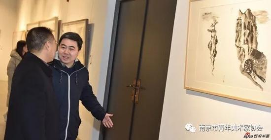 南京市青年美协秘书长徐锴向共青团南京市委副巡视员郑家芳介绍康斯但丁教授的作品