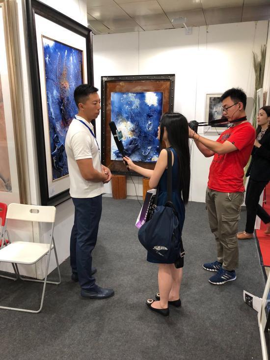 记者在展览现场采访司秋利先生的经纪人