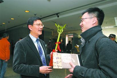 2015年大年初一早上,上博新馆长杨志刚(左)率工作人员迎候观众,向第一批进入大厅的参观者拜年并赠送新年小礼物。本报记者蒋迪雯摄
