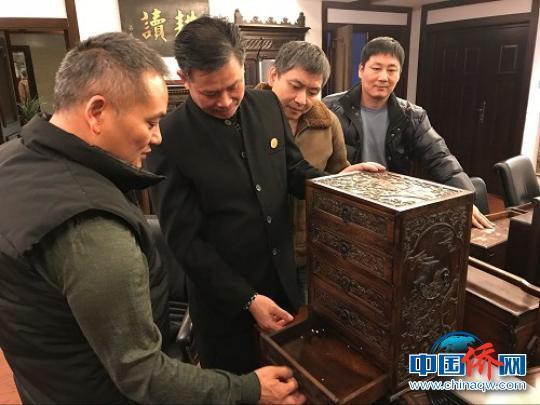 林文清(左)与众人欣赏一件木柜。 郑松波 摄