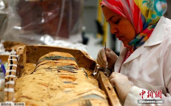 技术人员正在修复一具图坦卡蒙法老时期的木乃伊