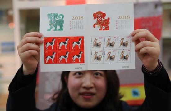 1月5日,在浙江省宁波市一邮政网点,工作人员展示《戊戌年》生肖邮票小版张。 新华社 图