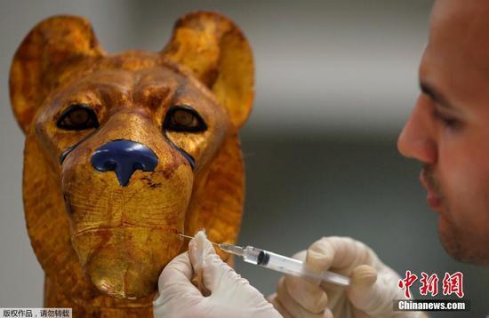 图为技术人员用化学试剂来修复图坦卡蒙法老床上的一个动物雕塑