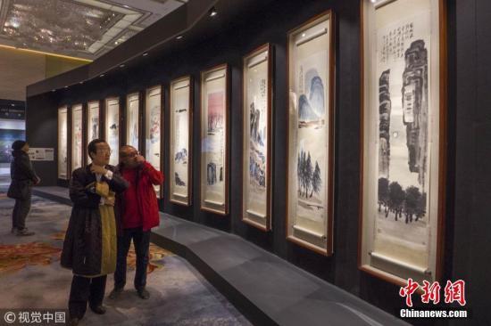 图为2017年12月6日,上海,观众在拍卖预展上欣赏《山水十二条屏》。 图片来源:视觉中国