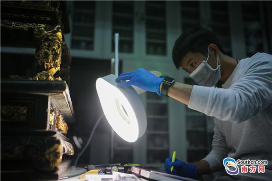 修复师在放大镜下观察潮州木雕。