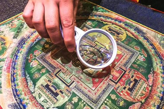 图为大师收藏的老唐卡,火气全无,看上去平和安详,佛像的精细处,要用放大镜才能一睹真颜。