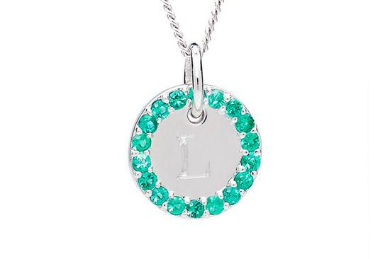 在这件铂金饰品上,字母的周围环绕着一圈祖母绿。