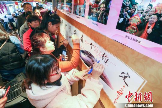 """近日,重庆客运段举行渝万高铁运行两周年庆祝活动。图为乘车旅客在""""我和渝万有个约定""""签名墙上签名留念,并写下对渝万高铁的祝福 包亮 摄"""