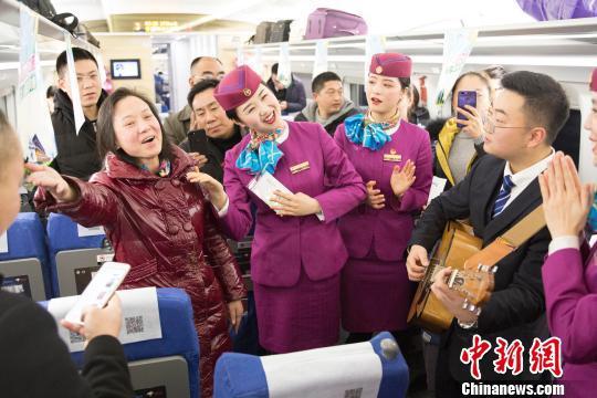 列车员与首发列车的旅客们一起联欢。 龚萱 摄