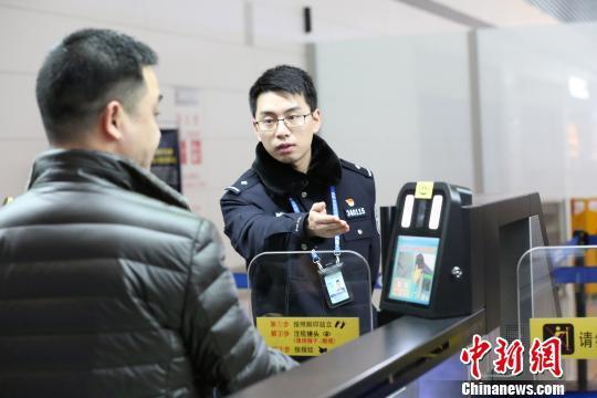 图为重庆重庆边检工作人员正在协助旅客办理边检自助查验手续。重庆边检供图
