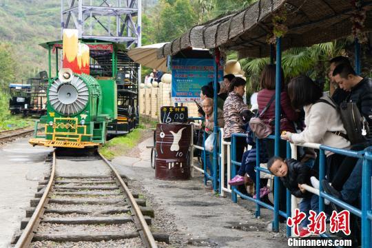 图为重庆洋人街景区,市民排队体验1元观光小火车。 钟旖 摄
