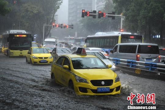 资料图为暴雨袭击重庆主城区,车辆通过积水路段。 陈超 摄