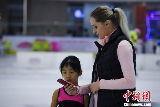 图为祝小雅与俄罗斯教练用翻译器交流。 韩璐 摄
