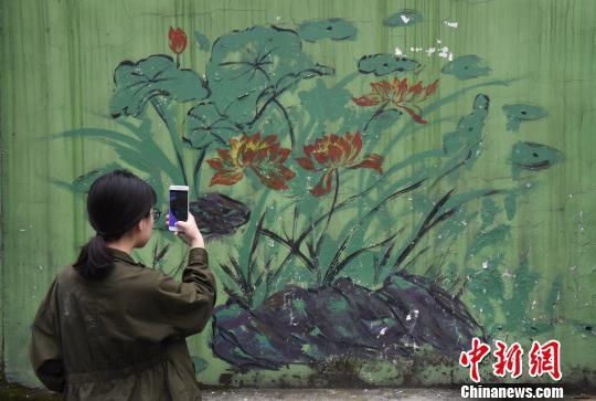"""图为""""牛皮癣""""墙壁上的画作吸引市民拍照留念。 周毅 摄"""