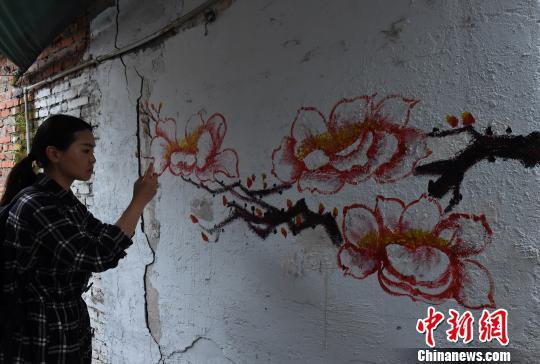 """图为环卫工人利用铲掉""""牛皮癣""""的墙壁作画,吸引市民驻足。 周毅 摄"""