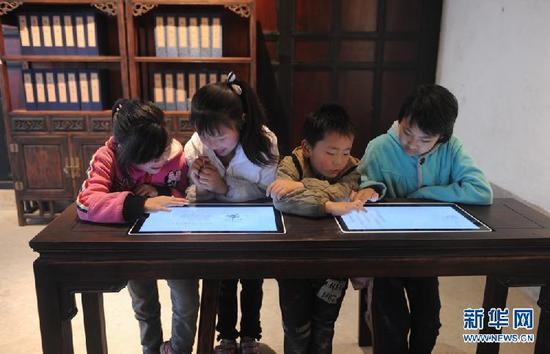 △会龙庄内,小朋友通过查询机了解私塾教学。