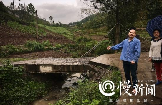 吕祖福的儿子在小桥前讲述自家多次建桥的经历。
