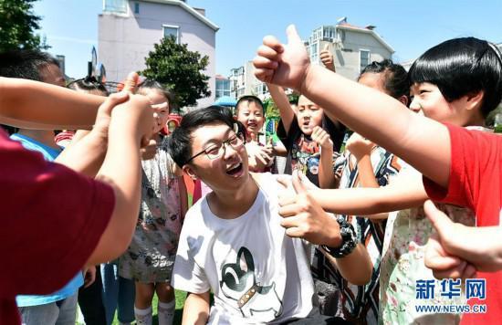 """陈叙良俨然是幼儿园里的""""孩子王"""",很受孩子们喜欢(9月4日摄)。新华社发(庄文斌 摄)"""