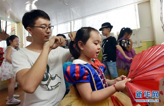 陈叙良正在给一名小姑娘扎辫子(9月4日摄)。 新华社发(庄文斌 摄)