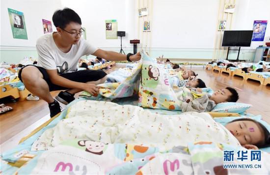 陈叙良给小朋友盖被子,同时不忘观察他们的午睡情况(9月4日摄)。新华社发(庄文斌 摄)