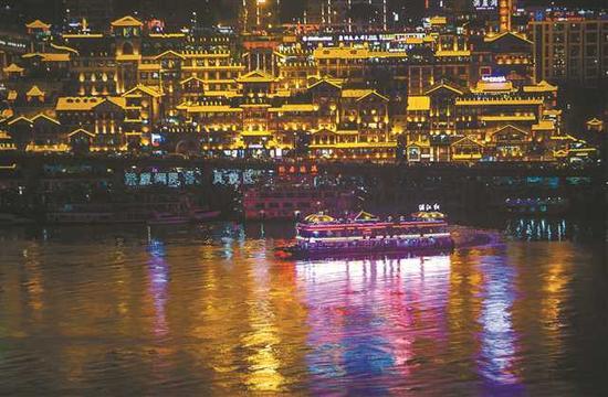 游客乘坐两江游船领略美丽的重庆夜景。