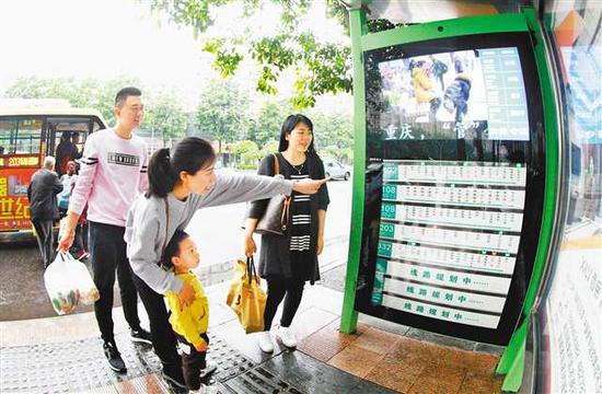 四月十三日,万盛经开区子如广场,市民通过电子智能公交站牌了解车辆信息。