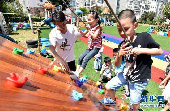 陈叙良在小心保护着体验攀岩游戏的孩子(9月4日摄)。新华社发(庄文斌 摄)